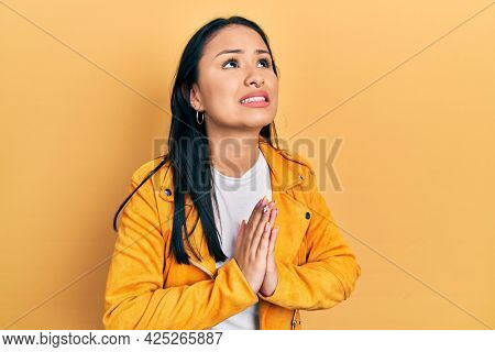 Beautiful hispanic woman with nose piercing wearing yellow leather jacket begging and praying with hands together with hope expression on face very emotional and worried. begging.