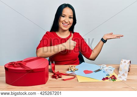 Beautiful hispanic woman with nose piercing doing handcraft creative decoration showing palm hand and doing ok gesture with thumbs up, smiling happy and cheerful