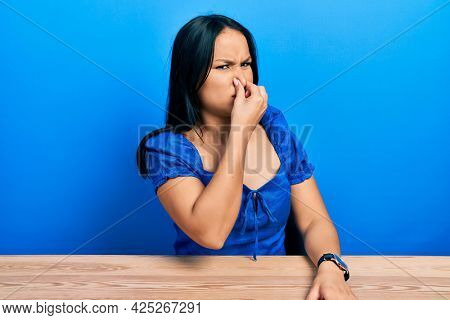 Beautiful hispanic woman with nose piercing sitting on the table smelling something stinky and disgusting, intolerable smell, holding breath with fingers on nose. bad smell