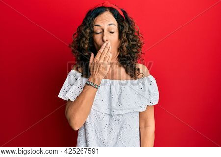 Middle age hispanic woman wearing casual clothes bored yawning tired covering mouth with hand. restless and sleepiness.