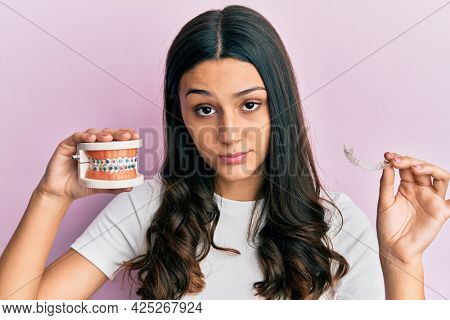Young hispanic woman holding invisible aligner orthodontic and braces skeptic and nervous, frowning upset because of problem. negative person.