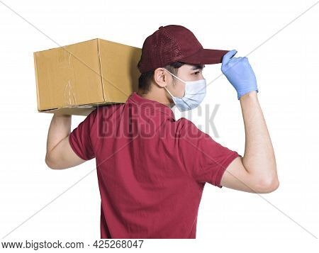 Young Couriers Wear Medical Masks  During The Covid-19 Epidemic. The Package Is Carried On The Shoul