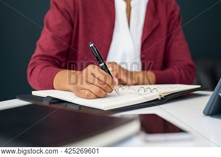 Hands of mixed race young woman writing notes on diary at home. Close up of african freelancer hands writing on notebook while working from home. Secretary writing in book during smart working.