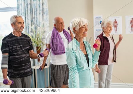 Group of old happy people using dumbbells for workout session at nursing home. Group of senior men and women exercising with dumbbells at gym of care centre. Eldelry doing workout using weights.