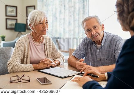 Senior man and woman meeting medical adviser for health insurance at home. Old couple planning their investments with financial advisor and prospectus. Aged couple consulting with insurance agent.