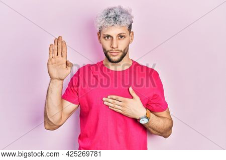 Young hispanic man with modern dyed hair wearing casual pink t shirt swearing with hand on chest and open palm, making a loyalty promise oath