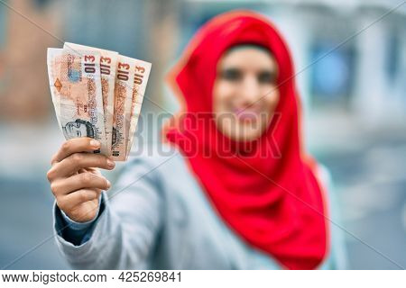 Young arab woman wearing hijab holding uk pounds at the city.