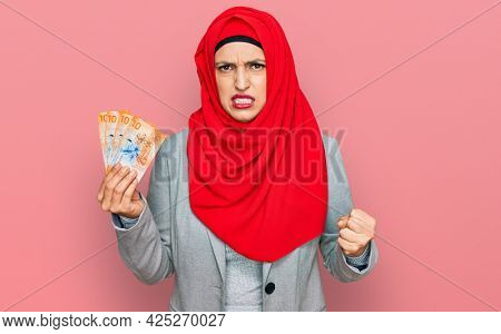 Beautiful hispanic woman wearing islamic hijab holding 10 swiss franc banknotes annoyed and frustrated shouting with anger, yelling crazy with anger and hand raised