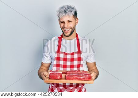 Young hispanic man with modern dyed hair holding board with raw meat winking looking at the camera with sexy expression, cheerful and happy face.