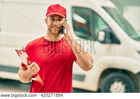Young caucasian deliveryman talking on the smartphone and holding clipboard at the city.