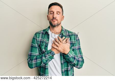 Handsome man with beard wearing casual clothes smiling with hands on chest with closed eyes and grateful gesture on face. health concept.