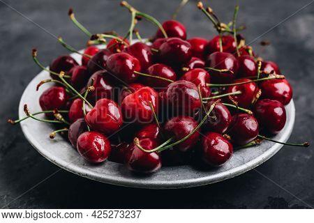 Cherry. Sweet Cherries In Bowl On Dark Stone Concrete Background.