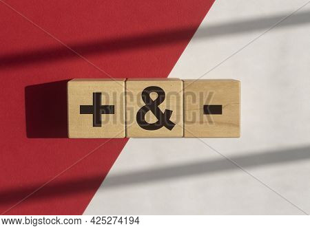 Plus And Minus Signs On Wooden Dices On White And Red Background With Daylight. Concept Of Positive