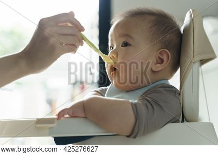 Mom With First Food Of Her Son. Asian Mother Feeding To Her Little Cute Baby Boy With Porridge Or Pu
