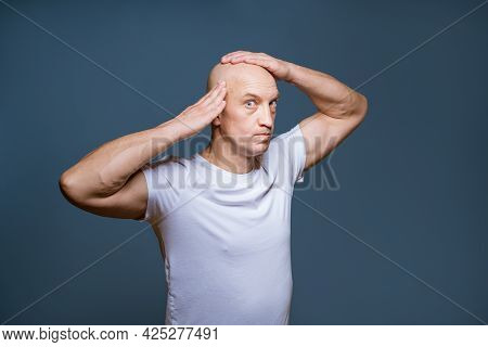 Funny Bald Man Posing On A Blue Background With Excited Facial Expressions And Raised Hands At His H