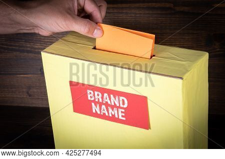 Brand Name. Yellow Ballot Box On A Wooden Background. Survey And Evaluation