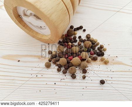 Scattered Black Pepper, Spices And A Spice Mill On A Light Background With A Wooden Texture. Ingredi