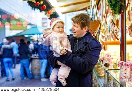 Middle Aged Father Holding Baby Daughter Near Sweet Stand With Gingerbread And Nuts. Happy Family On