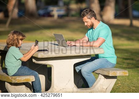 Father And Son Playing Or Studying With Laptop In The Park. Kid With Daddy Learning Lesson. Blogging