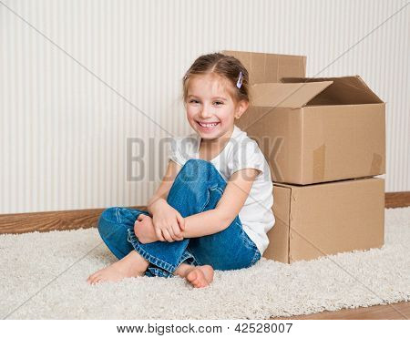 Little girl moving into new house, siting near  boxes