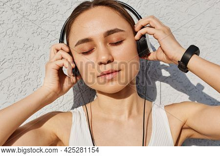 Young Adult Female With Dark Hair Wearing White Top, Keeping Eyes Closed, Touching Headphones With P
