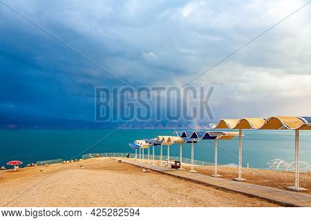 Israeli coast. The Dead Sea. Picturesque beach with bright sunshades. Gloomy sky with dark thunderclouds. The magnificent exotic resort for treatment and relaxation.