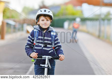 Active School Kid Boy In Safety Helmet Riding With His Scooter In The City With Backpack On Sunny Da