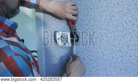 A Man In A Bright Shirt Works With Electrical Wires With The Help Of Tools, The Process Of Installin
