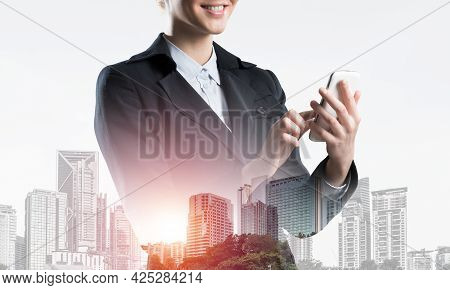 Young Businesswoman Using Mobile Phone. Double Exposure Concept With Modern Downtown Architecture An