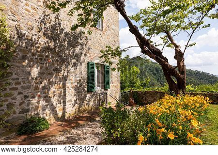 Detail of a wall of an ancient stone house with a flower garden aside.