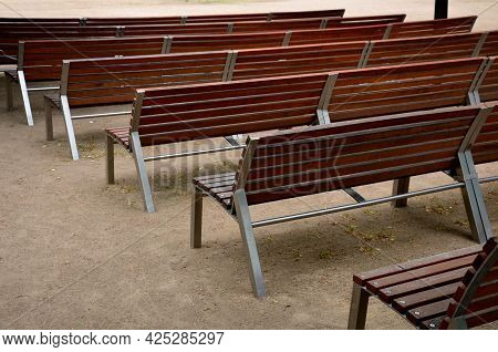 Outdoor Theater Auditorium. Benches Stacked In Rows. Adjacent. There Is An Alley Between The Wooden