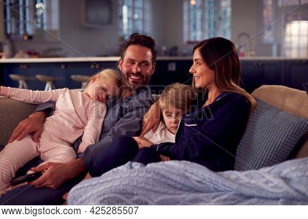Family In Pyjamas Sitting On Sofa Watching TV Together As Children Fall Asleep