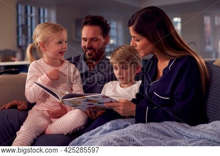 Family In Pyjamas Sitting On Sofa Reading Bedtime Story Together