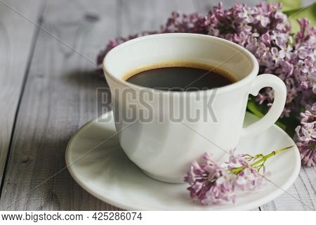 A White Cup Of Hot Coffee, A Branch Of Lilac