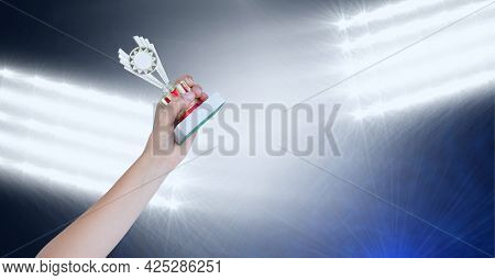 Close up of hand holding a trophy against stadium floodlights in background. sports tournament and competition concept