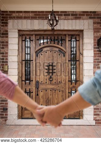 Couple Holding Hands Approaching Front Door of House.