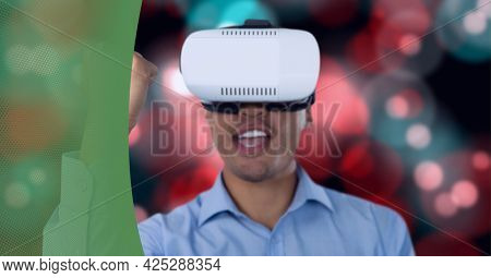 Man wearing vr headset against against red spots of light against green technology background. business and technology concept