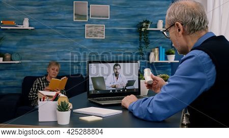 Telemedicine Consultation During Covid Pandemic, Man Sitting In Front Of Laptop In The Kitchen. Sick