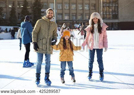 Happy Family Spending Time Together At Outdoor Ice Skating Rink