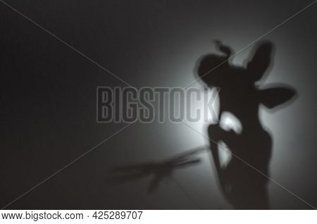 Abstract Defocused Silhouettes Of Fairy With Graceful Wings On A Gray Background. The Fairy Sits And