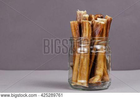 Pet Treats In A Glass Jar On A Gray-gainsboro Background. Dried Bully Sticks For Dogs. Beef Pizzle.