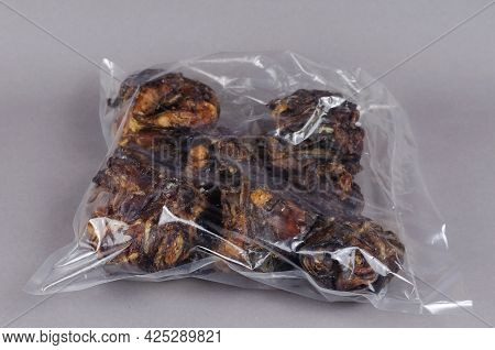 Air Dried Dog Treats On A Gray Background. Dental Treats In Transparent Packaging. Dried Beef Larynx
