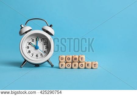 Alarm Clock And Cubes With Phrase Don't Forget On Light Blue Background, Space For Text. Reminder Co