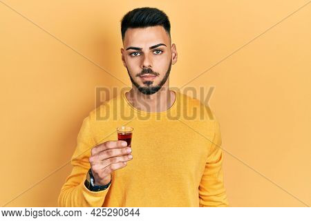 Young hispanic man with beard drinking whiskey shot thinking attitude and sober expression looking self confident
