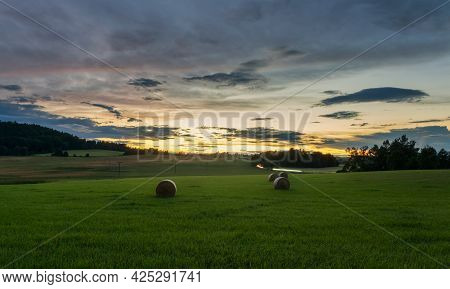 Haystacks On Meadow At Sunset, Czech Rural Landscape. Long Exposure With Car Ride On Street