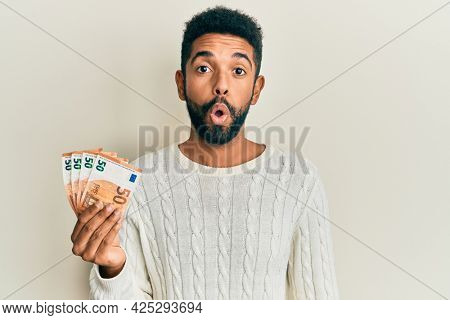 Handsome hispanic man with beard holding bunch of 50 euro banknotes scared and amazed with open mouth for surprise, disbelief face