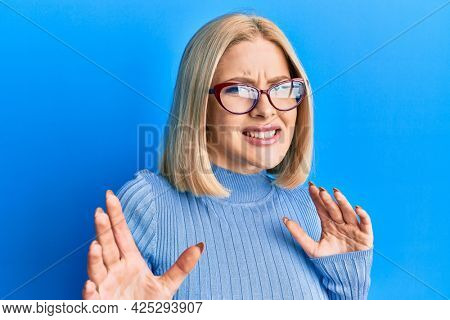 Young blonde woman wearing casual clothes and glasses disgusted expression, displeased and fearful doing disgust face because aversion reaction. with hands raised
