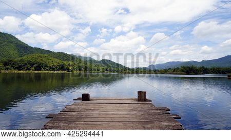 Wooden Pier On Lake In The Mountain. Panoramic View Of Wooden Bridge Lake With Green Mountain, Brigh
