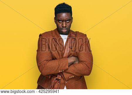 Handsome business black man wearing leather bag skeptic and nervous, disapproving expression on face with crossed arms. negative person.