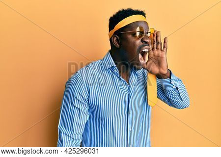 Handsome black man drunk wearing tie over head and sunglasses shouting and screaming loud to side with hand on mouth. communication concept.